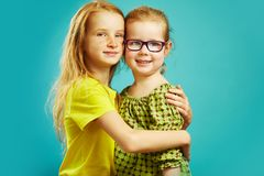 Older redhead sister ten years younger is hugging the cousin with spectacles. Warm relations between children Stock Image