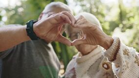 Older retired couple making heart with their hands. Selective focus