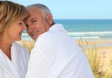 Older in the sand dunes. Older couple smooching in the sand dunes Royalty Free Stock Image