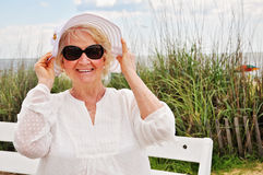 Older senior lady wearing hat and sunglasses at beach Royalty Free Stock Images