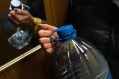 Older senior woman`s hand holding a big blue plastic bottle in an elevator stock photos