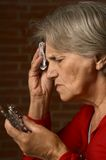 Older sick woman in red Royalty Free Stock Photos