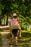 Older sister carries the younger sister on her back. Younger sister got tired of walking in nature, near the river Royalty Free Stock Photos