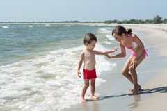 Older sister gives hand to younger little brother on the seashore stock photos