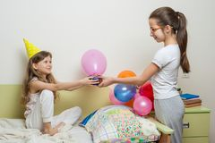 Older sister giving surprise gift to her cute little sister. Birthday morning. Older sister giving surprise gift to her cute little sister. Children at home in royalty free stock image
