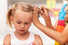 Older sister helps little girl tie her hair in plaits. While playing, shallow depth stock photography