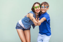 Older sister and her brother with freckles, posing over  blue background together, looking at camera with toothy smile and thumbs Royalty Free Stock Photography