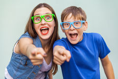 Older sister and her brother with freckles, posing over light blue background together, looking at camera with pointing fingers. Royalty Free Stock Photos