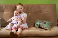 Older sister holds  little younger Royalty Free Stock Image