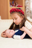Older sister hugging baby lying on the bed Stock Images