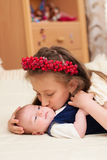 Older sister hugging baby lying on the bed Stock Photo