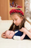 Older sister hugging baby lying on the bed Royalty Free Stock Images