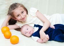 Older sister hugging baby lying on the bed with oranges Royalty Free Stock Photo