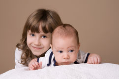 Older sister hugging her baby brother. On beige background Royalty Free Stock Images