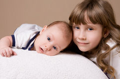 Older sister hugging her baby brother. On beige background Royalty Free Stock Image