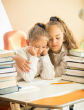 Older sister hugging sad younger one at class Stock Images