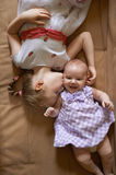 Older sister kissing the younger lying on  couch Royalty Free Stock Photography