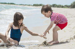 Older sister with little brother are built of sand on the seashore, Stock Image