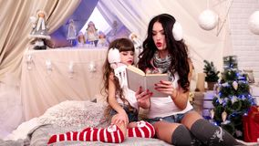 Older sister read together with the younger, The girls read the book, stock video