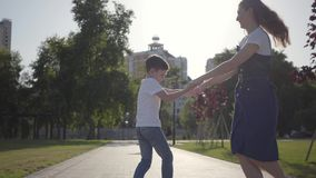 Older sister spinning around with younger brother holding hands in the summer park. Leisure outdoors. Friendly relations. Older sister spinning around with stock footage