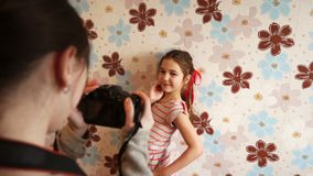 Older sister takes pictures of younger. Older sister taking pictures of younger against the background of the wall with flowers stock video