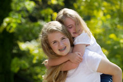 Older sister taking care of her younger sister while outdoors Royalty Free Stock Image