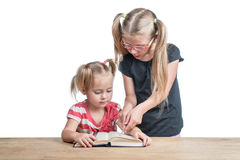 Older sister teaches the younger. Senior sister teaches the younger to read a book lying on a wooden table isolated on a white background Stock Image
