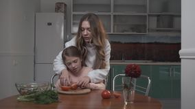 Older sister teaches younger sister to cut tomatoes for salad. Two sisters cocking vegetable salad while sitting at the stock footage