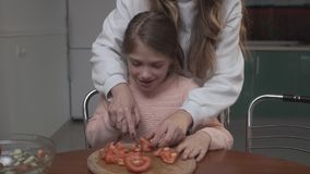 Older girl teaches younger girl to cut tomatoes for salad. Two sisters cocking vegetable salad while sitting at the stock footage