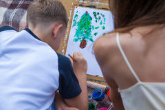 Older sister trying to teach her brother to paint in the park Stock Photography