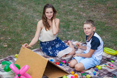 Older sister trying to teach her brother to paint in the park Royalty Free Stock Image