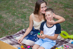 Older sister trying to teach her brother to paint in the park Stock Photos