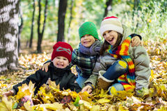 Older sister and two younger brothers in autumn leaves Happy. Stock Photography