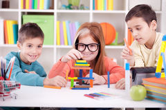 Older sister and two younger brothers  play with wooden blocks a Stock Image