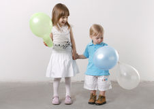 Older sister and younger brother. On a white background holding balloons Stock Photos