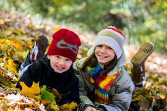 Older sister younger brother playing in autumn leaves, happy, Stock Images