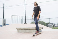 Older skateboard enthusiast skating around in skate park Stock Image