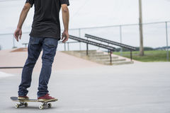 Older skateboard enthusiast skating around in skate park Royalty Free Stock Photography