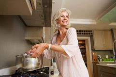 Older smiling woman boiling water on kitchen stove top Stock Photo