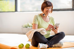 Older sports woman with smartphone indoors royalty free stock image