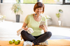 Older sports woman with smartphone indoors royalty free stock photography
