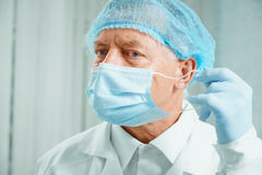 Older surgeon takes off his mask Stock Photography