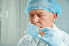 Older surgeon takes off his protective mask. Tired older man surgeon takes off his protective mask after operation Royalty Free Stock Photography