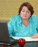 Older teacher looking at her computer