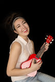 Older teen girl playing ukulele sitting and smiling Royalty Free Stock Photography