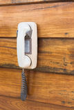 Older telephone hanging on wall. Stock Photo