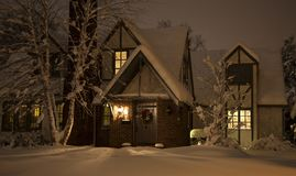 Cozy House in Snow at Night Royalty Free Stock Image