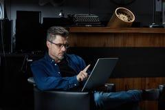 Older white man sitting in dark room using tablet Stock Photo