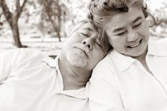 During older wife get happy at the park, her older husband is pass away by heart attack. Old woman doesn't know it. Grandma royalty free stock photo