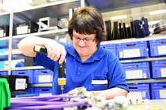 Older woman assembles electronic components in a hi tech factory royalty free stock image